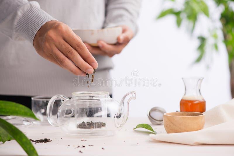 Té sano de colada Té caliente en una tetera de cristal en una tabla de madera fotografía de archivo