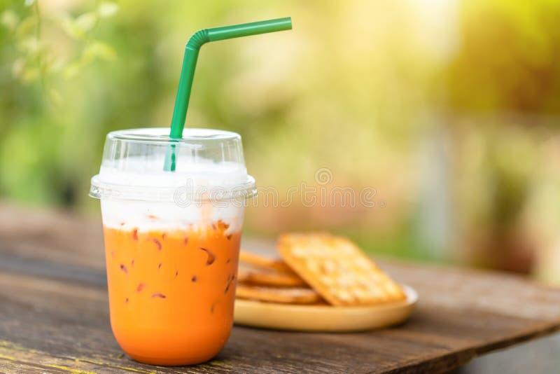 Té tailandés helado en la taza del plástico transparente servida en la tabla de madera en café del jardín foto de archivo libre de regalías