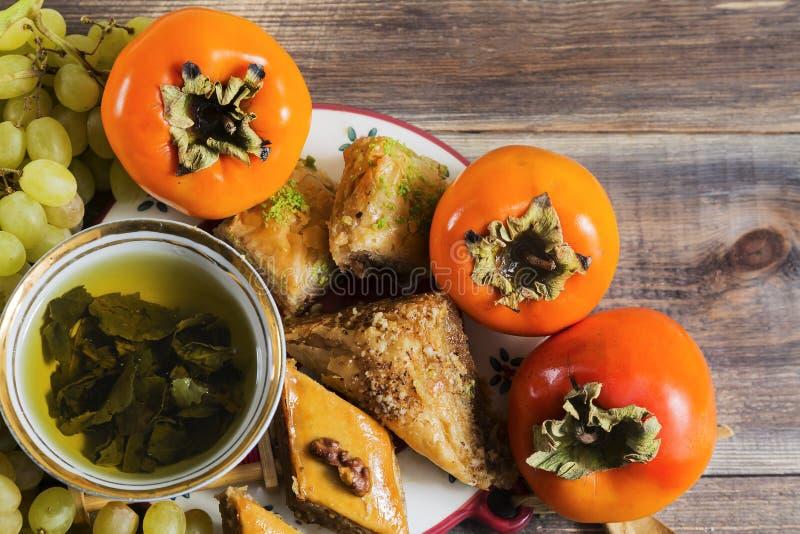 Té verde del desayuno del este con los encantos, caquis, uvas en superficie de madera imagen de archivo