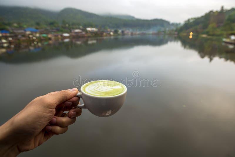Té verde del latte caliente de Matcha en la taza blanca a mano con el pueblo del agua en el borde de la opinión del río foto de archivo