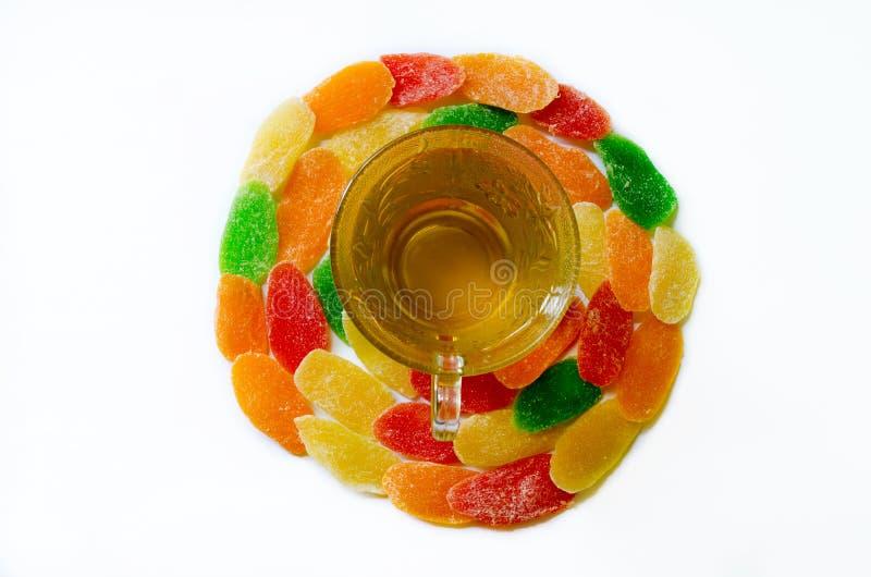 Té verde en la taza de cristal con los dulces - piña escarchada en blanco foto de archivo