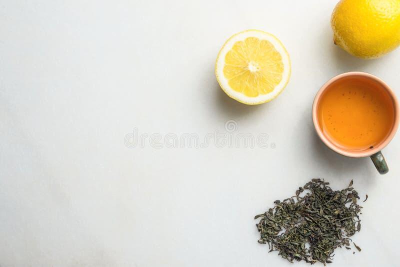 Té verde preparado en taza de cerámica De hojas sueltas dispersados en la rebanada de piedra de mármol blanca del fondo de limón  imagen de archivo