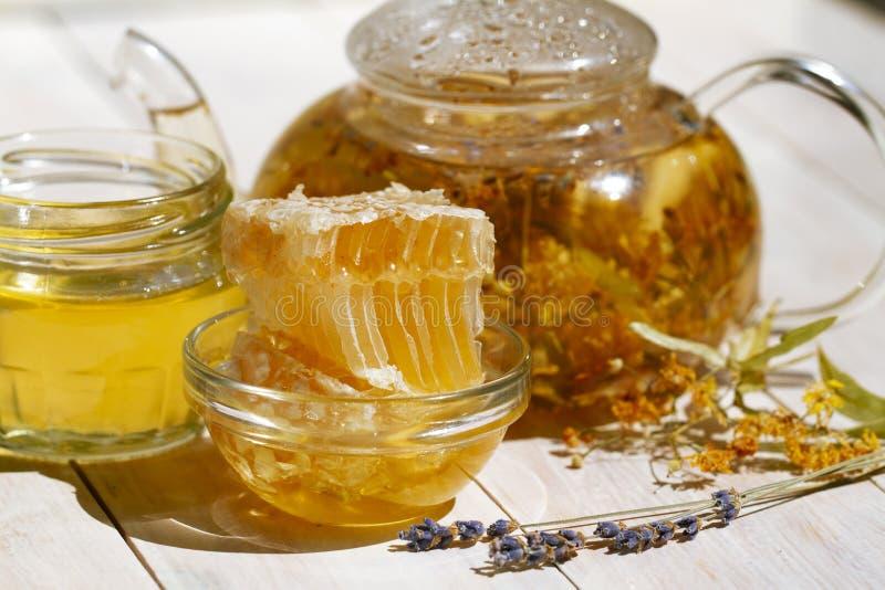 Té y flores de la lavanda del tilo de la tetera en la tabla de madera blanca con el peine de la miel y el tarro frescos de miel f fotos de archivo libres de regalías