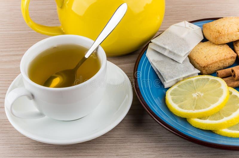 Té y placa con las rebanadas de limón, de canela y de galletas imagen de archivo