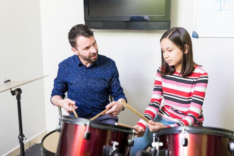 Técnica de Teaching Drum Playing do instrutor à menina imagens de stock royalty free