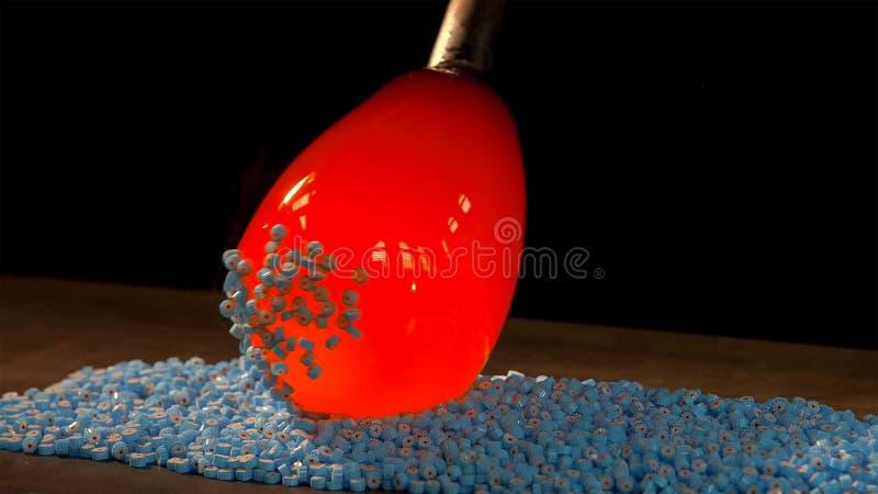Técnica de vidro de Murano no processo: haste de ferro com objeto de vidro unido após o sopro na fornalha a fim adicionar cores a fotos de stock