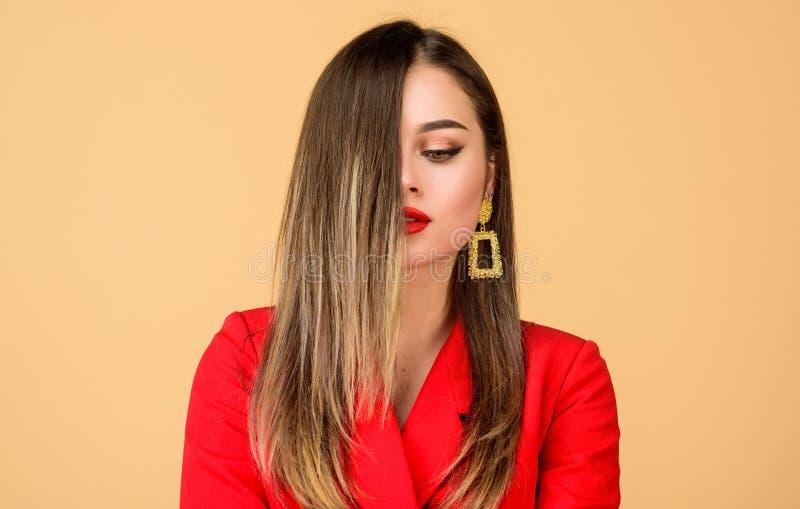 Técnica del color del pelo de Balayage Labios rojos de la mujer de la cara bonita del maquillaje La mujer lleva los pendientes at imagenes de archivo