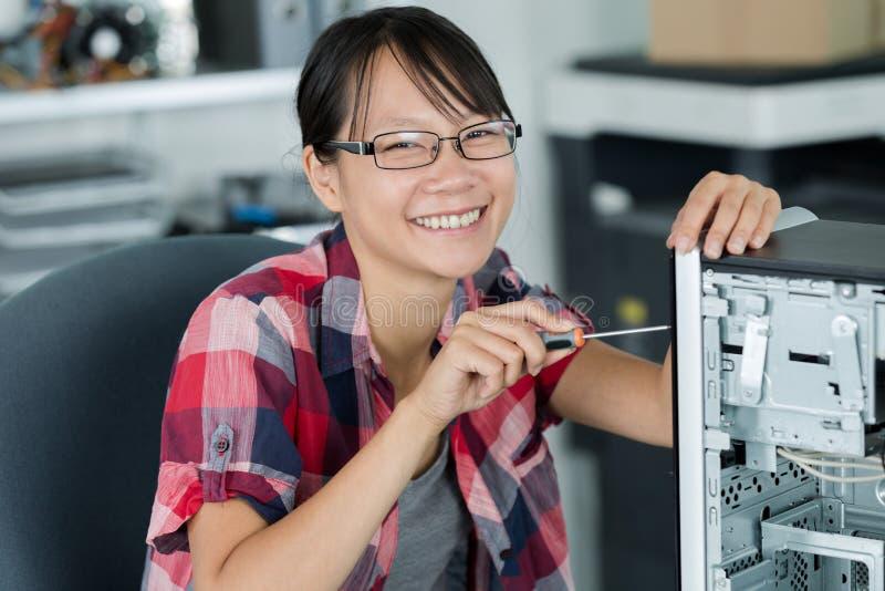 Técnico asiático fêmea que trabalha no computador imagem de stock