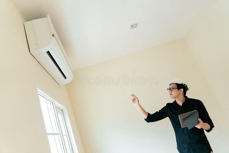 Técnico asiático que comprueba el acondicionador de aire foto de archivo libre de regalías