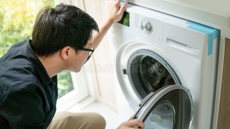 Técnico asiático que olha na máquina de lavar fotografia de stock royalty free