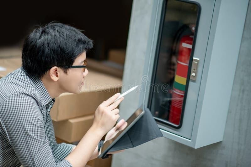 Técnico asiático que verifica o armário da mangueira de fogo fotos de stock royalty free