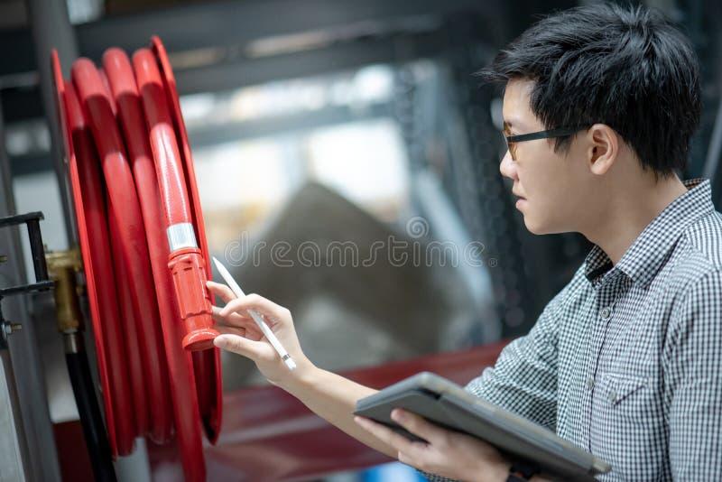 Técnico asiático que verifica o carretel da mangueira de fogo imagem de stock royalty free