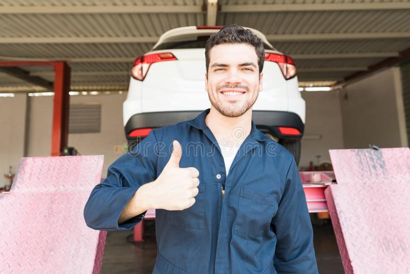 Técnico bem sucedido Showing Thumbs Up do automóvel na loja fotos de stock royalty free