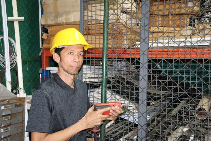 Técnico com posição amarela e perfurador do capacete à disposição e funcionamento na área fotos de stock royalty free