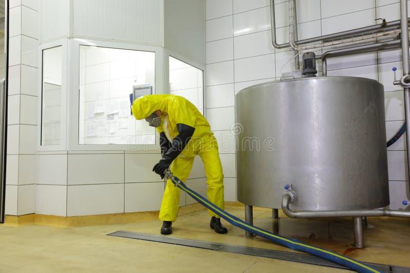Técnico con la manguera grande en el tanque industrial en planta foto de archivo libre de regalías