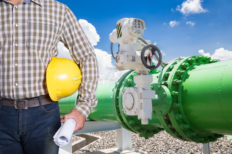 Técnico da manutenção com as válvulas do encanamento do sistema da água refrigerando foto de stock