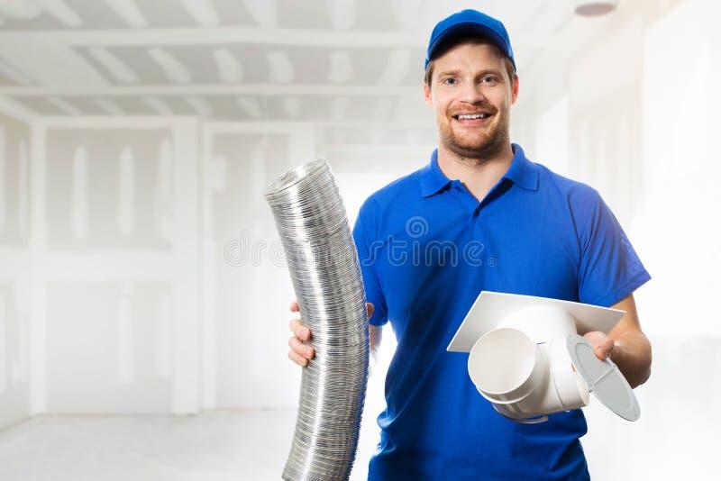 Técnico de la HVAC listo para instalar el sistema de ventilación en casa imagenes de archivo