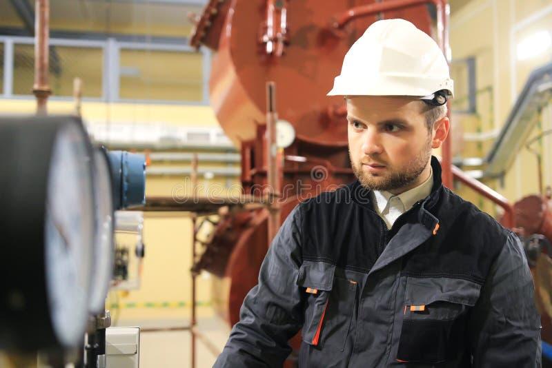 Técnico de la HVAC que comprueba el indicador de presión en fábrica industrial Ingeniero que supervisa los manómetros imágenes de archivo libres de regalías