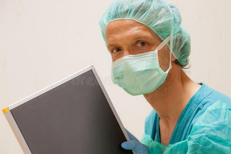 técnico de la radiología con el cassetteGoogle radiográfico Traduttore fotos de archivo
