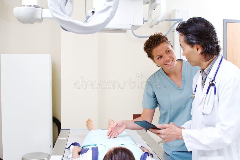 Técnico de la radiología con el paciente y el médico fotos de archivo libres de regalías