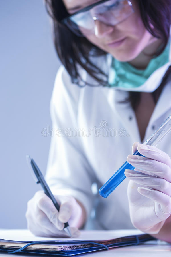 Técnico de laboratório fêmea Dealing With Flask que contém produtos químicos líquidos fotos de stock