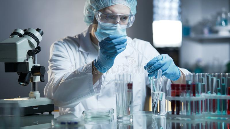 Técnico de laboratório que mede a fórmula exata para produtos cosméticos hypoallergenic imagens de stock
