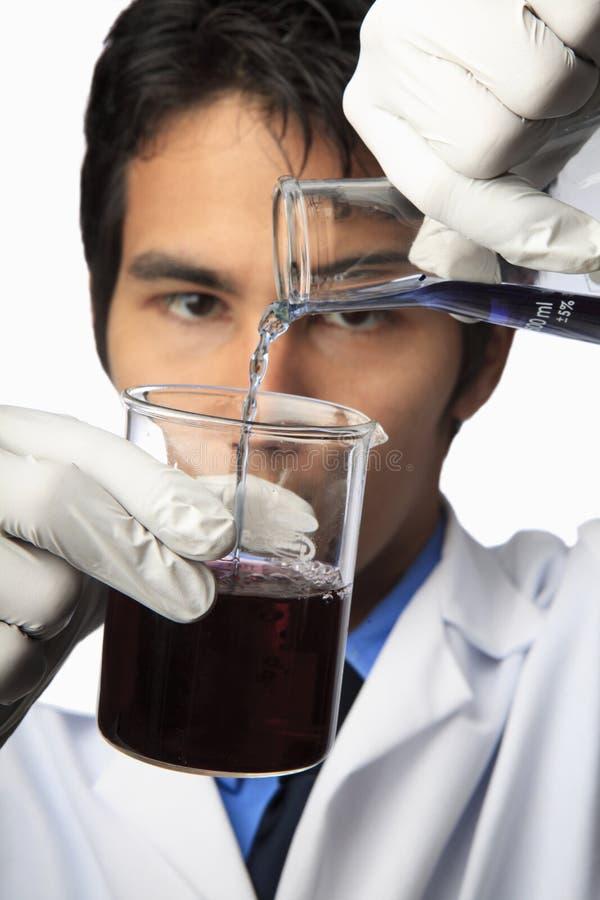 Técnico de laboratorio con el cubilete y el frasco fotografía de archivo