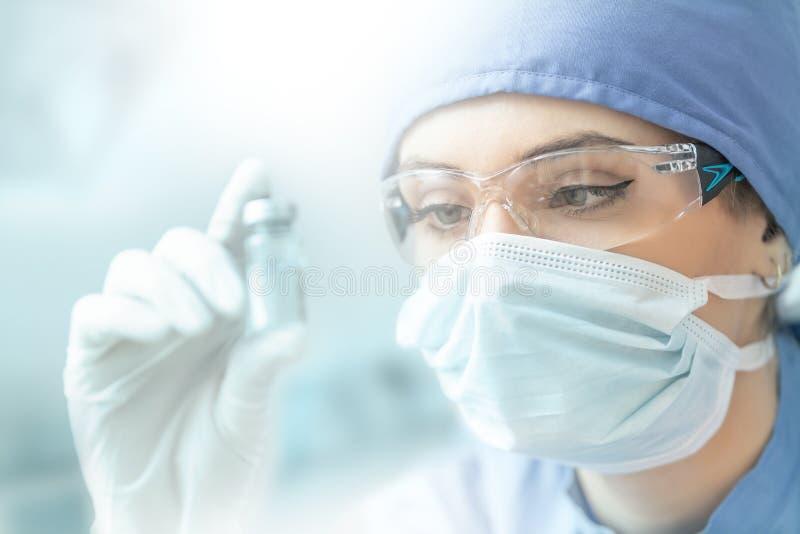 Técnico de laboratorio femenino con ampolla de vacuna de virus imagen de archivo