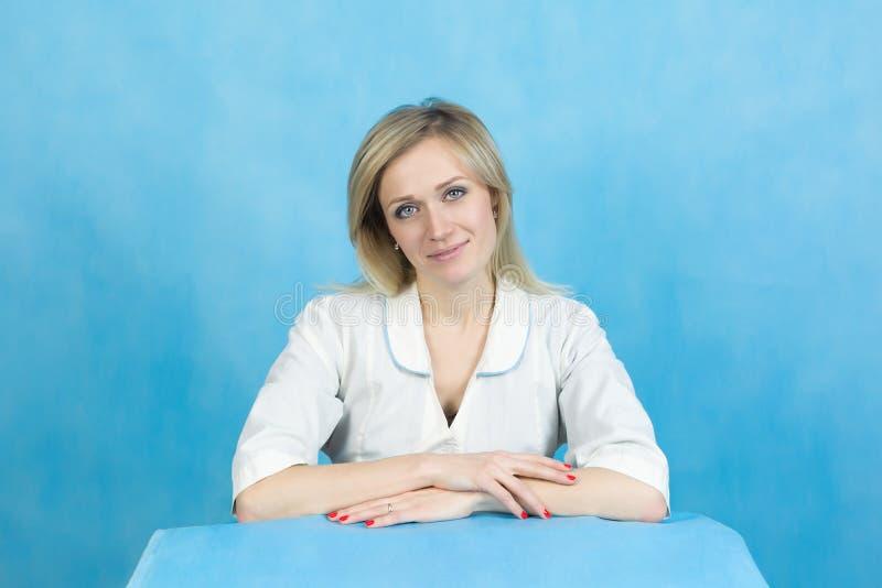 Técnico de laboratorio de la muchacha en un fondo azul fotografía de archivo