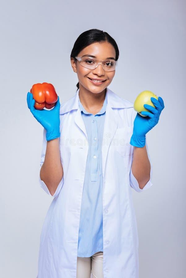 Técnico de laboratorio optimista que presenta con paprika y la manzana foto de archivo