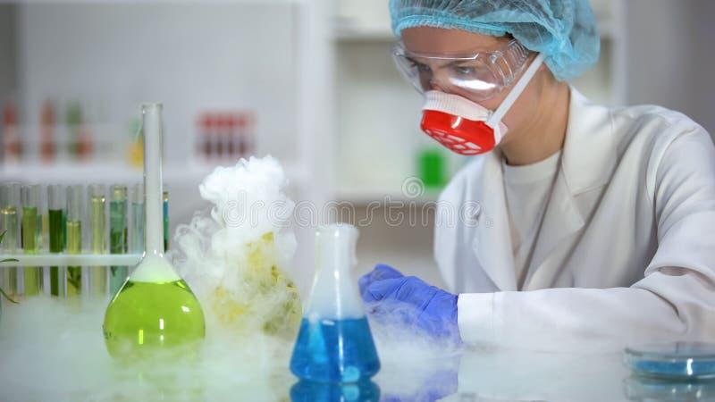 T?cnico de laboratorio que comprueba la reacci?n de frascos que fuman con los l?quidos coloreados imagenes de archivo