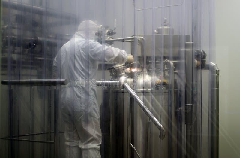 Técnico de laboratorio que lleva la ropa protectora en installationss de la fábrica de la droga foto de archivo