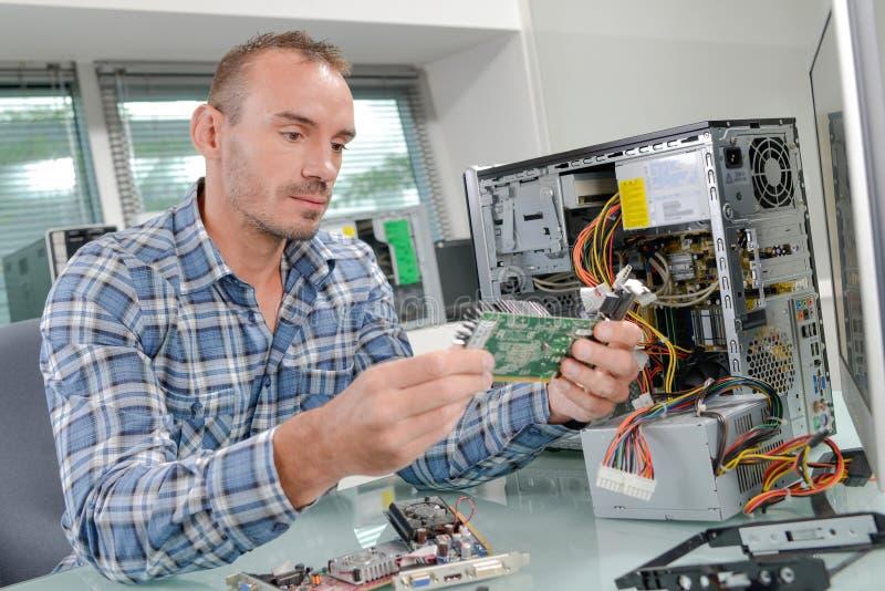 Técnico de las TIC que repara el equipo de escritorio roto de la PC fotos de archivo libres de regalías