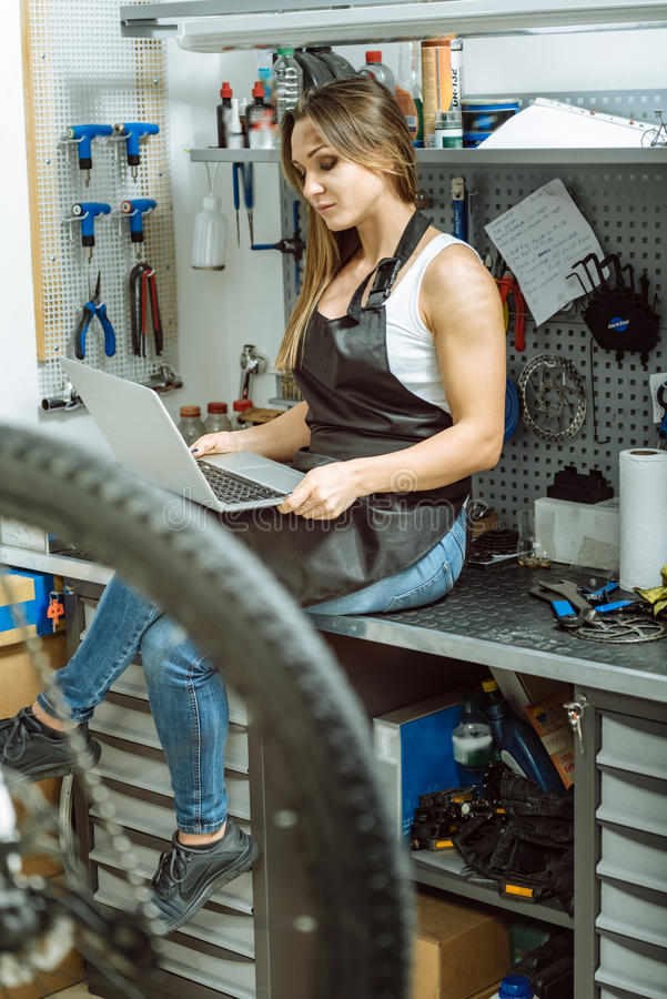 Técnico de sexo femenino encantador que usa el ordenador portátil en el taller de reparaciones foto de archivo