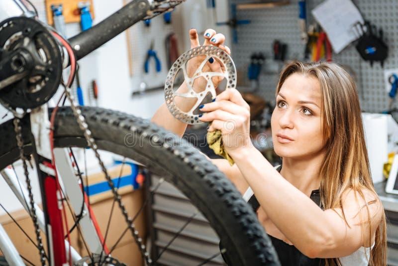 Técnico de sexo femenino pensativo que sostiene la rueda dentada en el garaje imagenes de archivo