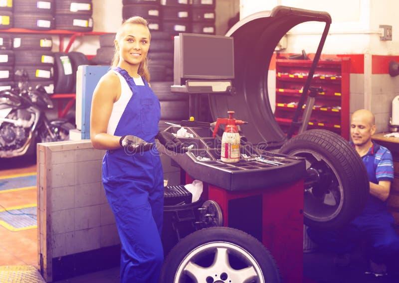 Técnico de sexo femenino que se coloca con maquinaria de equilibrio de la rueda en el aut foto de archivo libre de regalías