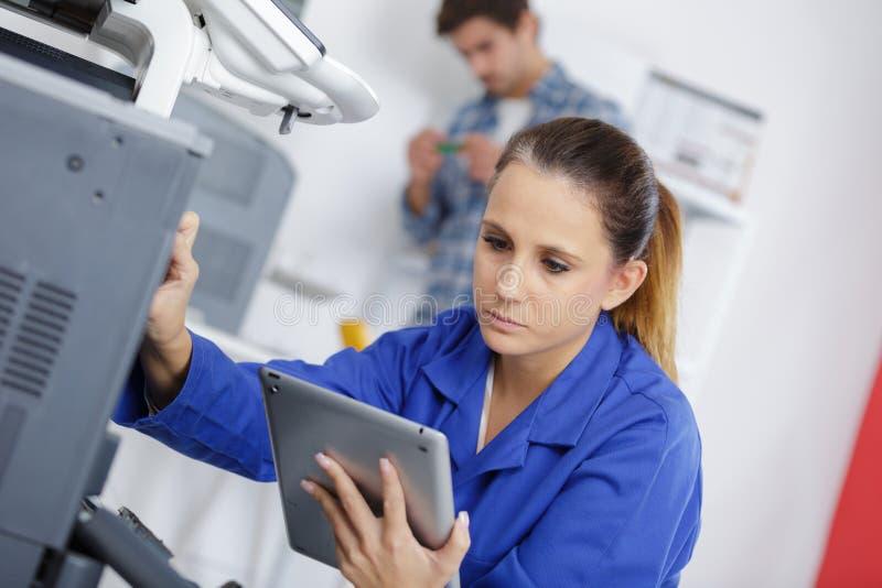 Técnico de sexo femenino que trabaja en la tableta de la tenencia de la fotocopiadora imagenes de archivo