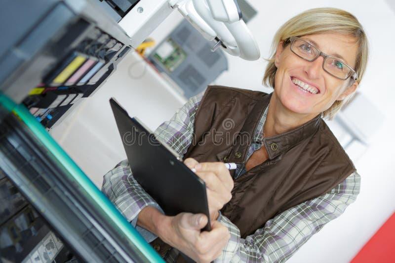 Técnico de sexo femenino sonriente de los jóvenes en los guardapolvos que sostienen el tablero foto de archivo libre de regalías
