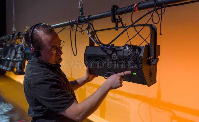 Técnico de sexo masculino del teatro que ajusta el engranaje imagenes de archivo
