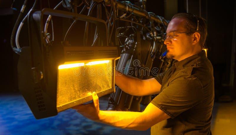 Técnico de sexo masculino del teatro que ajusta el engranaje fotografía de archivo libre de regalías