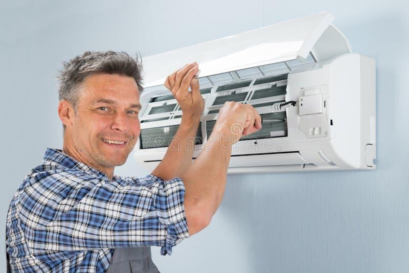 Técnico de sexo masculino que repara el acondicionador de aire fotos de archivo