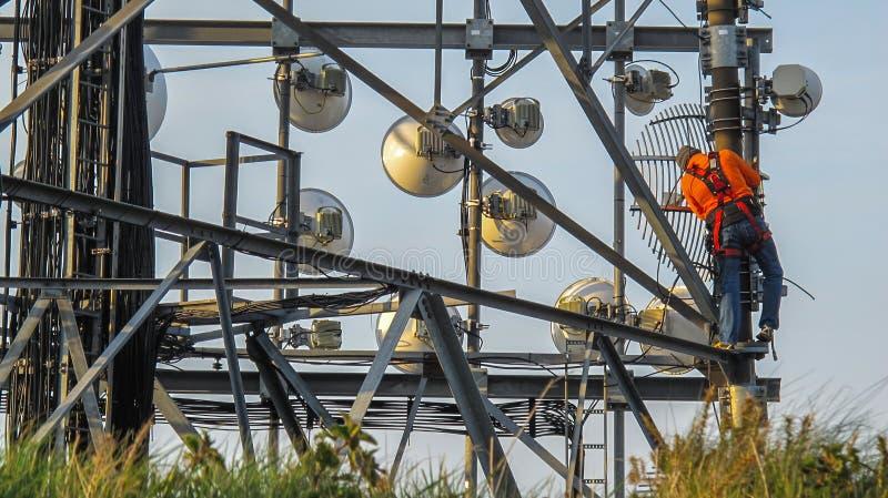 Técnico de trabalho acima de uma torre das telecomunicações imagem de stock