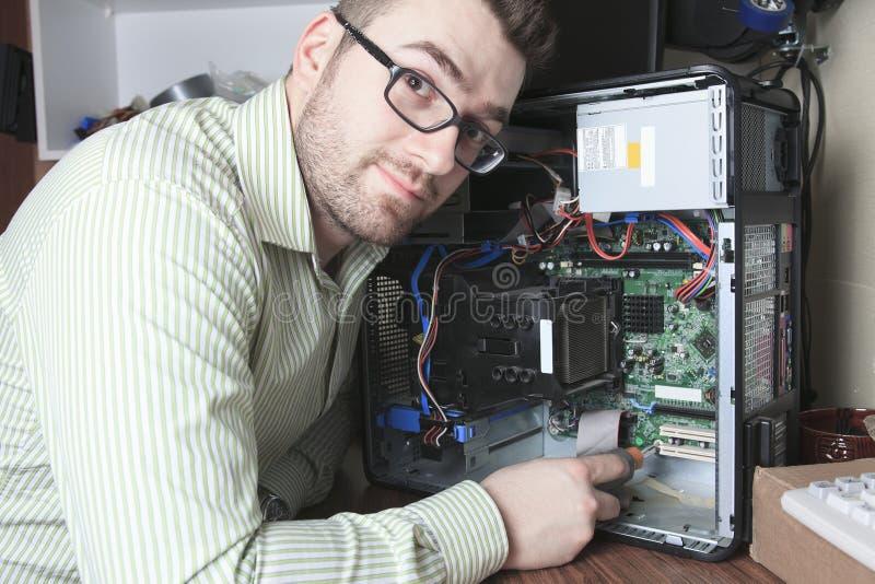 Técnico del trabajador en el trabajo con el ordenador fotos de archivo