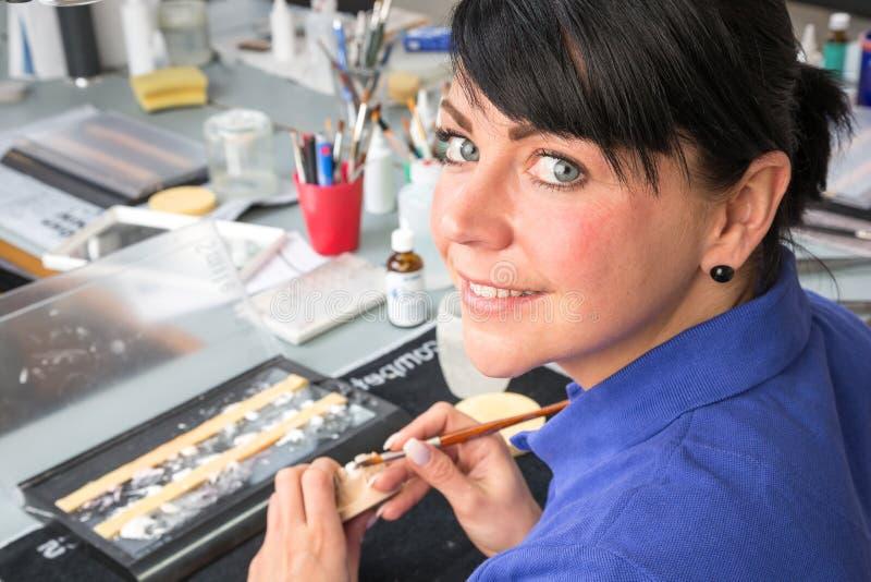Técnico em um laboratório dental que aplica a cerâmica a uma prótese fotos de stock royalty free