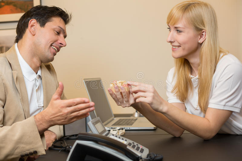 Técnico dental que mostra a prótese a um cliente fotos de stock