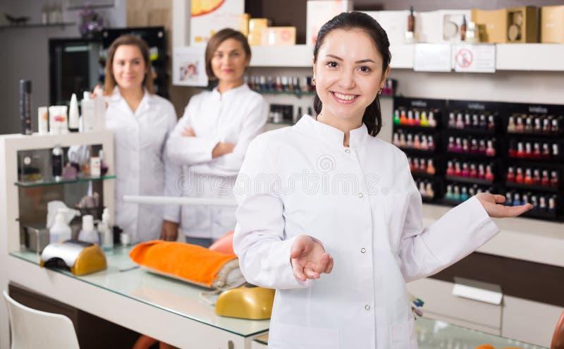 Técnico do prego que dá boas-vindas ao salão de beleza imagem de stock