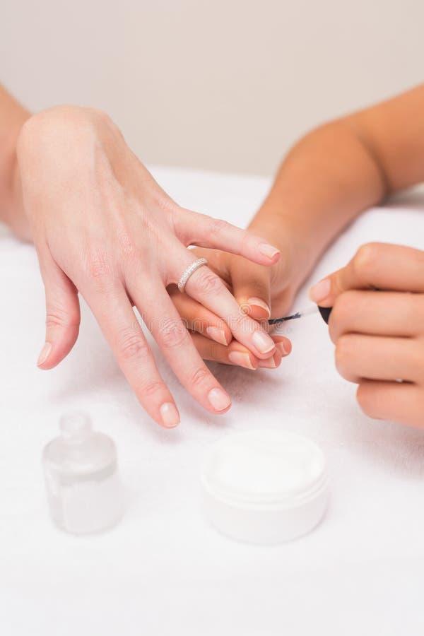 Técnico do prego que dá a cliente um tratamento de mãos imagens de stock