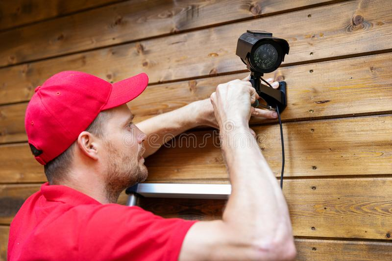 Técnico do sistema de segurança que instala a câmara de vigilância na parede de madeira da casa fotografia de stock