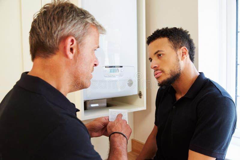 Técnico e aprendiz da caldeira que prestam serviços de manutenção à caldeira doméstica fotografia de stock royalty free