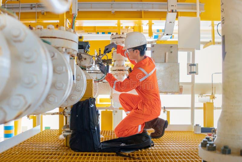 Técnico eléctrico e instrumental reparan la válvula en la plataforma, el mantenimiento y el servicio de procesamiento de petróleo imagen de archivo